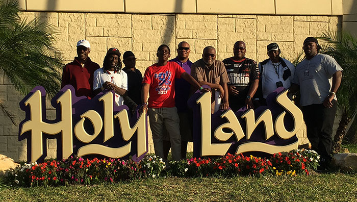 "men in front of a sign that says ""Holy Land"""