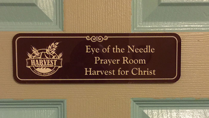 Sign that says Eye of the Needle Prayer Room Harvest for Christ on a door