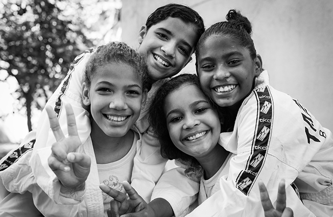 black and white photo of four children smiling and hugging